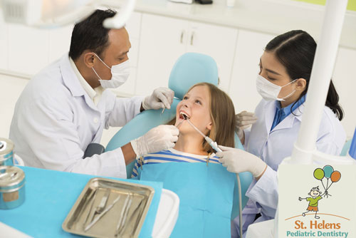 A small girl being treated with a dental sealant to prevent cavities.