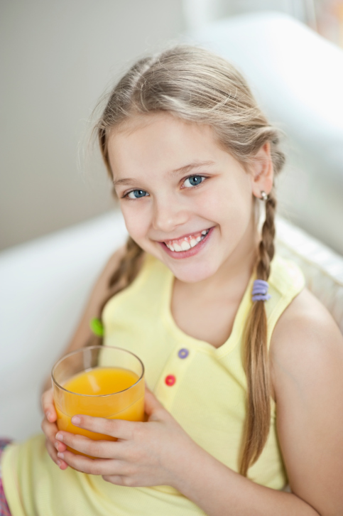 A young girl drinking a sugary orange juice.