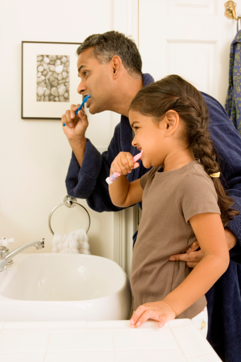 A father watching how his daughter brushes her teeth.