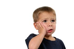 Little boy hand on face with a toothache